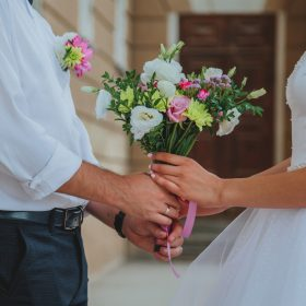 Newlyweds holding bouquet of wedding flowers